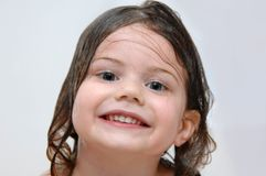 Grinning During Bath Time. Little girl gives a big grin during bath time. Her hair is wet and she is in a white bath tub stock photography