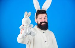 Grinning bearded man wear silly bunny ears. Easter symbol concept. Hipster cute bunny long ears blue background. Easter. Bunny. Funny bunny with beard and royalty free stock photo