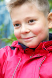 Grinning boy. In red jacket closeup photo selective focus Royalty Free Stock Photography