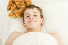 Grinning boy in bed covered with blanket. Single grinning young teen boy laying in bed on pillow just waking up next to brown furry plush toy Royalty Free Stock Photography