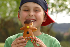 Grinning  boy with a doughnut. Happy boy holding an iced doughnut Stock Photography