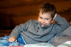 Grinning boy lying on the bed. The little guy in a gray sweater and blue jeans lies on a bed, resting the head on an elbow and grins. The image in a low key Stock Photo