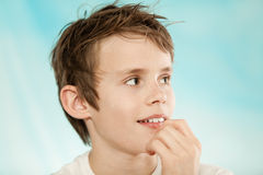 Grinning boy with messy hair and hand near mouth Royalty Free Stock Images