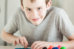 Grinning boy pressing into clay. Single happy boy with grin in gray shirt pressing into clay pieces of various colors with fingers on table Stock Photo
