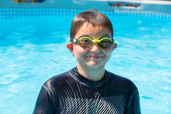 Grinning boy in swim shirt and goggles at pool. Soaked single grinning boy in swim shirt and goggles at outdoor swimming pool during summer season Stock Photography