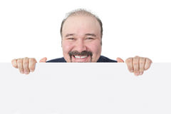 Grinning businessman holding a blank white sign Royalty Free Stock Photography