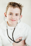 Grinning child checking his pulse with stethoscope Stock Photos