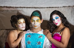 Grinning Cirque Clown with Admirers. Grinning cute cirque performer with female admirers stock photography