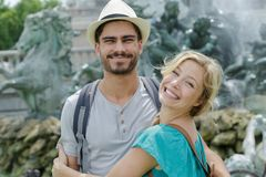 Grinning couple posing by tourist landmark. Couple royalty free stock images