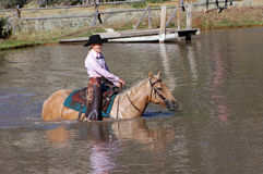 Grinning Cowgirl Crossing Pond. On palomino horse stock images