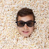 Grinning, flaunt young boy in stereo glasses looking out of popcorn Stock Photography