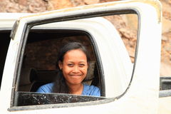 Grinning girl in car window. Grinning Papuan girl - young woman sitting in a white off-road car and watching thru opened window royalty free stock photo