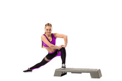 Grinning girl doing shaping exercise on stepper Stock Image