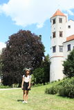 Grinning girl in front of tower of castle in Telc Stock Photos