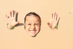 Grinning girl looking thru hole royalty free stock photography