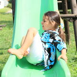 Grinning girl on a slide. Grinning little girl in blue-black-white t-shirt and white shorts playing on green slide royalty free stock images