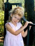 Grinning and Happy. Young girl holds onto a black iron gate.  She has on a light pink dress that is sleeveless.  She has long blonde hair Stock Photo
