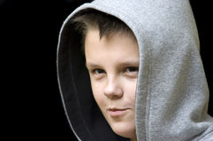 Grinning hooded boy. Portrait of a grinning, slighly smiling hooded teenager, isolated on black background. More expressions with this model available from that Stock Photos