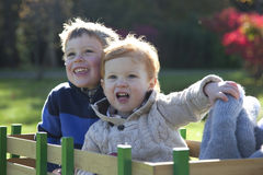 Grinning kids. Brothers sit in wagon and smile, grin outside in the fall royalty free stock photo