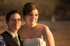 Grinning Lesbian Newlyweds. Grinning gay married couple outside after wedding royalty free stock photos