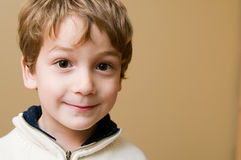 Grinning little boy. Little boy in studio grinning at the camera Royalty Free Stock Photo