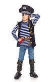 Grinning little boy pirate. Full length little boy wearing pirate costume posing with hand on hat, looking away, over white background Stock Photo
