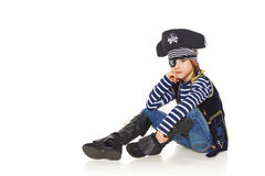Grinning little boy pirate. Full length little boy wearing pirate costume sitting on the white studio floor, over white background Stock Images