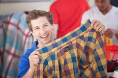 Grinning Man Holding Shirt Royalty Free Stock Photos