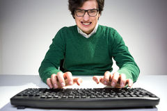 Grinning man using keyboard Royalty Free Stock Photos