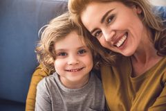 Grinning mommy and son are having nice time at home. Portrait of happy family looking at camera and smiling indoors. Parent is tenderly bonding her child Royalty Free Stock Photos