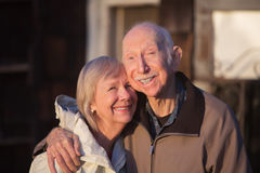 Grinning Older Couple. Embracing while standing outdoors stock image