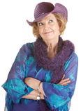Grinning Senior Lady. Cheerful mature woman in hat with folded arms Royalty Free Stock Photography
