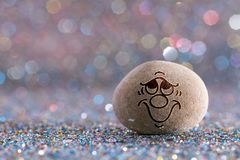 The grinning stone emoji. Emotions on color glitter boke background royalty free stock image