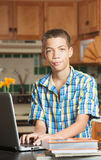 Grinning teen with laptop and textbooks Stock Photo