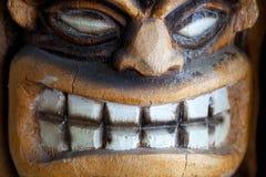 Grinning tiki. Closeup of smiling tiki carving statue stock photo
