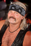 Grinning Tough Guy. Grinning middle aged man with leather vest and bandanna royalty free stock photos