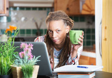 Grinning woman in kitchen with homework and laptop Stock Photos