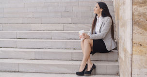 Grinning woman on stairs drinking coffee Stock Image