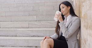 Grinning woman on stairs drinking coffee Royalty Free Stock Image