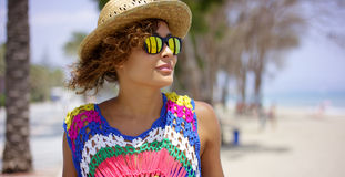 Grinning woman in sunglasses and hat near ocean Royalty Free Stock Photography