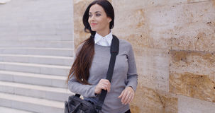 Grinning woman in sweater near wall looking over Stock Image