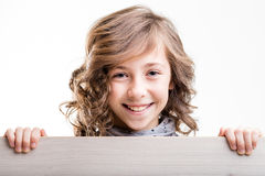 Grinning young blond haired girl. Young blond haired girl grinning while holding painted wooden board Royalty Free Stock Images