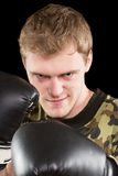 Grinning young man in boxing gloves Stock Image