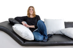 Grinning young woman is sitting on a black and white couch Royalty Free Stock Photo