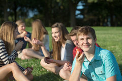 Grinning Youth With Apple. Happy group of teenagers eating healthy snacks outdoors Royalty Free Stock Photos