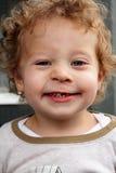 Grinsen des 2 Jahr-alten blonden Jungen, der einen Zahn verfehlt Stockbilder
