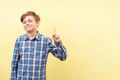 Grinsen des Jungen, der zeigt, um einzuwenden oder zu simsen, Schablone lizenzfreies stockfoto