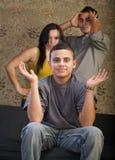 Grinsender junger Mann mit verärgerten Muttergesellschaftn stockfoto