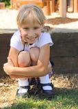 Grinsendes kleines blondes Mädchen, das in einem Spielplatz spielt Stockbild