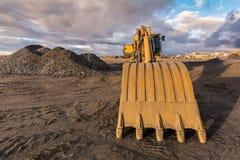 Grintberg in een steengroeve met zware machines voor zijn beweging stock fotografie